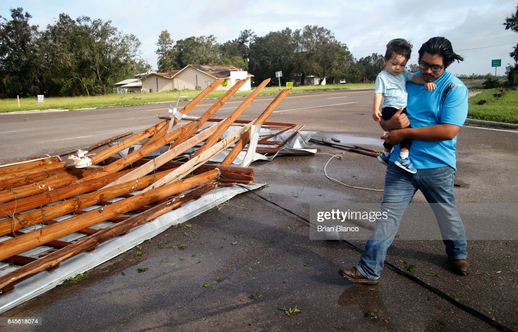 Gonzalo Saldivar and his one year-old son Luke get their first look at the roof that flew off of their home and landed at a nearby intersection during the high winds caused by Hurricane Irma on September 11, 2017 in Bowling Green, Florida. Hurricane Irma made landfall as a Category 4 storm twice in the United States on Sunday after tearing a path across islands in the Caribbean Sea.