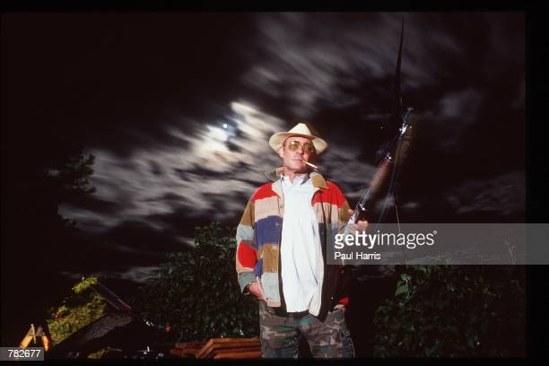 Gonzo journalist Hunter S Thompson stands on the balcony of his home at midnight with one of his pet peacocks beside him September 1990 in Woody...