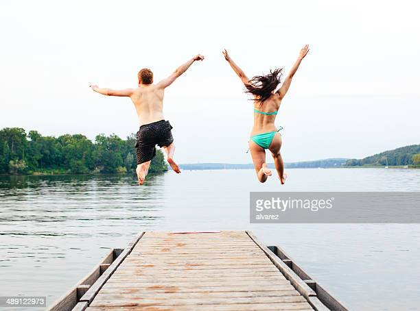 Good friends jumping into the lake