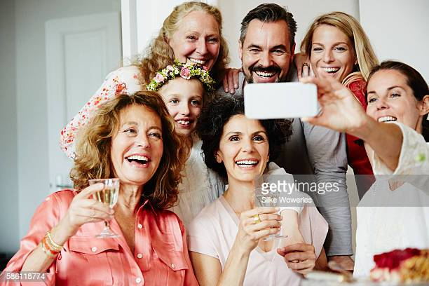 good friends taking a self-portrait with a smartphone at a party