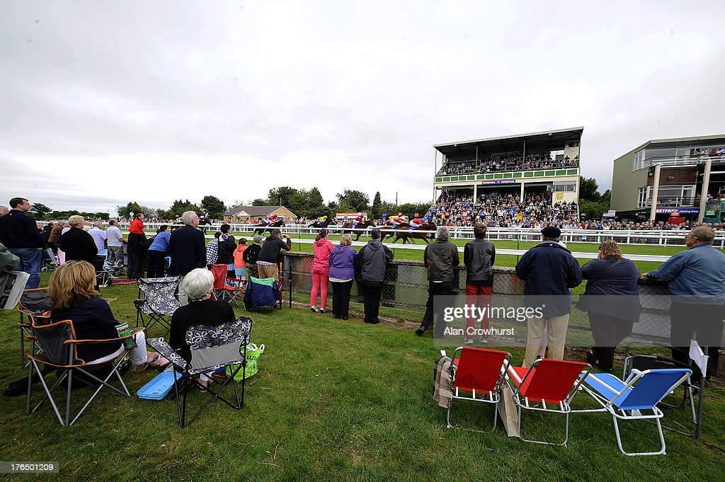 A good holiday crowd watch the action from the Silver Ring at Salisbury racecourse on August 14, 2013 in Salisbury, England.