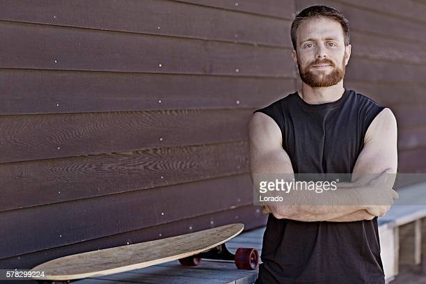 Good looking casual skateboarder male posing at summer beach location