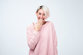 Good looking young female with dyed hair wearing pink sweater giggles joyfully, covers mouth as tries stop laughing, on gray background. Happy woman recieves proposal from boyfriend