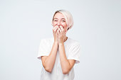 Good looking young female with dyed hair wearing white t-shirt giggles joyfully, covers mouth as tries stop laughing, on gray background. Happy woman recieves proposal from boyfriend