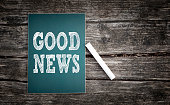 Good news text written on a chalkboard on wood background