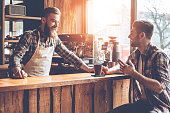 Barista and his customer discussing something with smile while sitting at bar counter at cafe