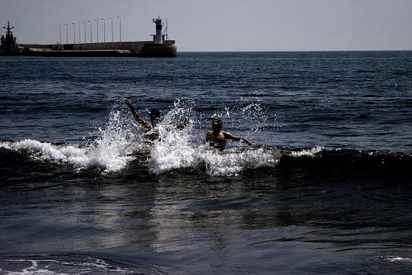 Refugees and Migrants bathe next to the port of Piraeus