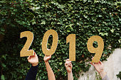 """Shot of a group of people holding the numbers """"2019"""" together"""