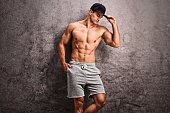 Good-looking shirtless guy with a blue cap leaning against a rusty gray wall and looking down