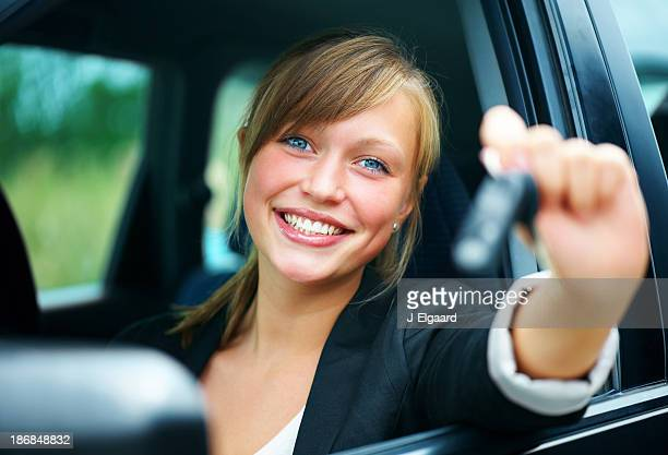 goodlooking woman with keys of new, hire or rental car