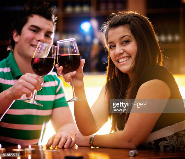 Good-looking young couple in bar raise glasses in toast