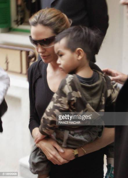 Goodwill Ambassador and US celebrity actress Angelina Jolie carries her adopted son Maddox as she walks out of an orphanage in Beirut 23 December...