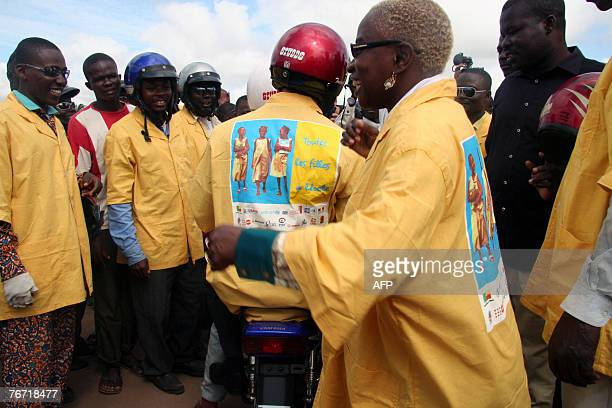 UNICEF goodwill ambassador Beninese singer Angelique Kidjo meets with motorbike taxi drivers wearing jackets promoting the campaign for the schooling...