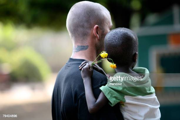 Goodwill Ambassador David Beckham carries fiveyearold Foday during a tour of a therapeutic feeding centre on January 19 2008 in Makeni Sierra Leone...