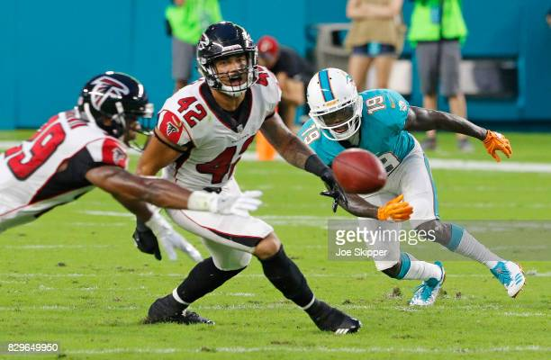 J Goodwin of the Atlanta Falcons left Duke Riley of the Atlanta Falcons and Jakeem Grant of the Miami Dolphins reach for a loose ball in the first...