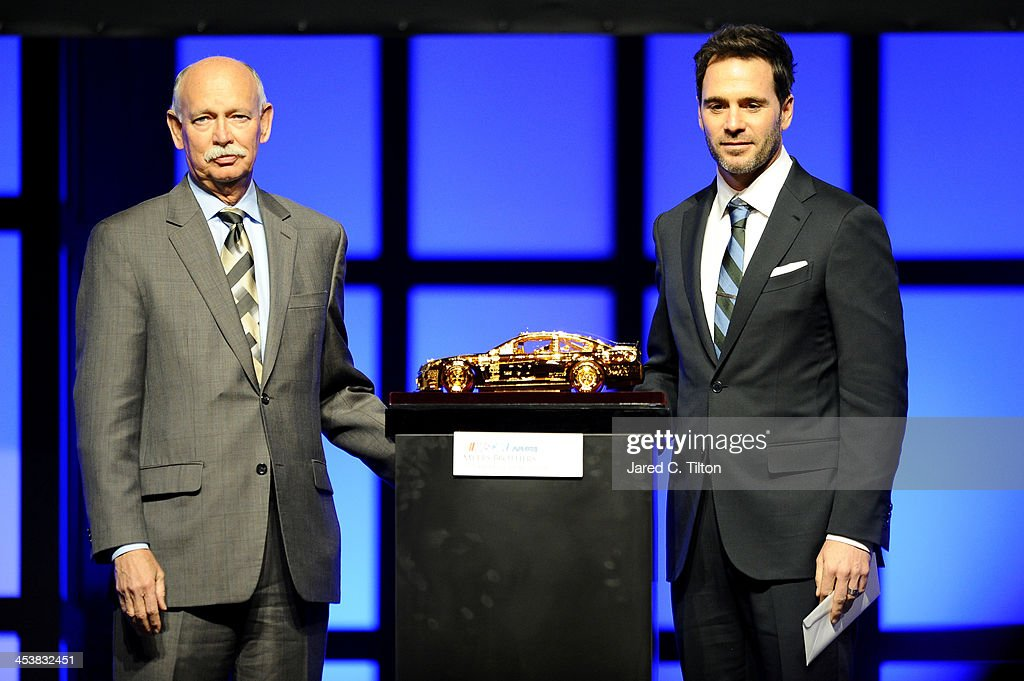 Goodyear General Manager of Global Race Tires Stu Grant and NASCAR Sprint Cup Series Champion Jimmie Johnson pose onstage after Johnson wins the Goodyear Tires Award at the NMPA Myers Brothers Awards Luncheon at the Encore Las Vegas on December 5, 2013 in Las Vegas, Nevada.