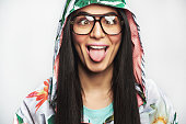 Goofy young woman wearing eyeglasses and a hooded anorak squinting and sticking out her tongue in a close up cropped head shot isolated on white
