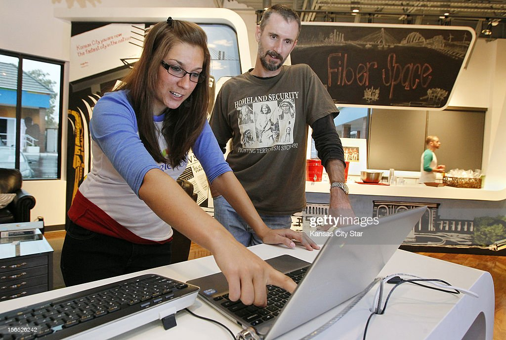 Google announces the build-out schedule for qualifying fiberhoods, September 13, 2012. In the Google Fiber office, Christina Komonce, left, a team member, helps Jeff Dalin find out when it will reach the Edison School fiberhood in which Dalin is registered.
