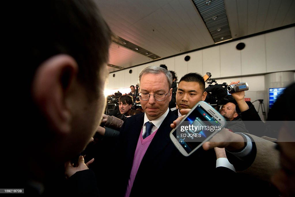 Google chairman Eric Schmidt (C) surrounded by the media after arriving at Beijing airport from North Korea on January 10, 2013 with former New Mexico governor Bill Richardson (not pictured). Richardson and Schmidt met with reporters following their visit to secretive North Korea calling for greater Internet freedom for the welfare of its people. AFP PHOTO / Ed Jones