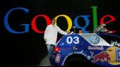 Google cofounder Larry Page rides on the back of a car as he makes his entrance to deliver his keynote address at the International Consumer...