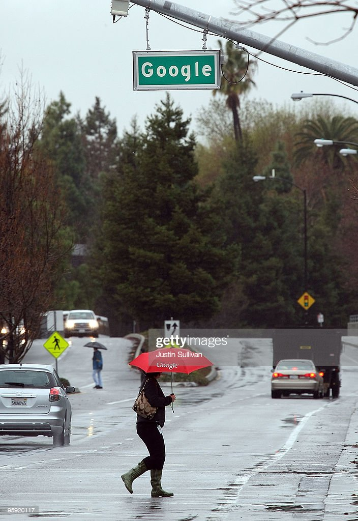 A Google employee carries a Google umbrella as she crosses the street outside of the Google headquarters January 21, 2010 in Mountain View, California. Google will report fouth quarter earnings today.