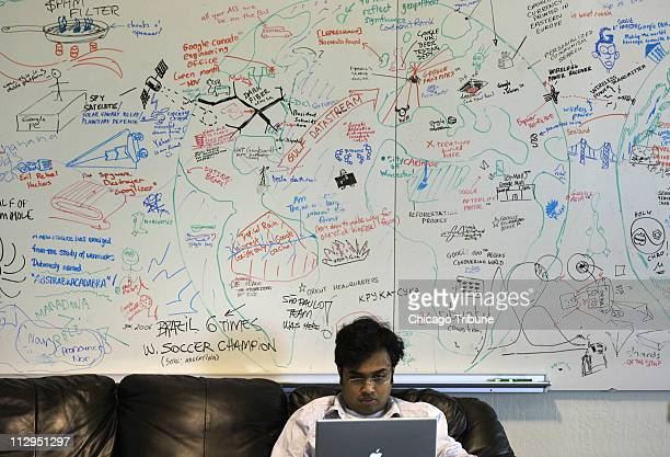 Google employee Pranay Gupta works on his laptop in front of a white board used for creative thinking at White boards such as these are scattered...