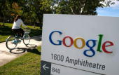 Google employee rides a bicycle by a sign at the company's headquarters October 18 2007 in Mountain View California Google reported today that third...