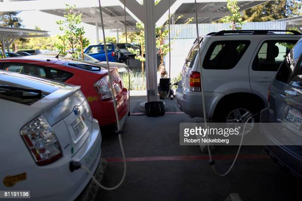 Google employee sends a computer email near one of the many electric cars owned and leased by the company on April 15 2008 in Mountain View...