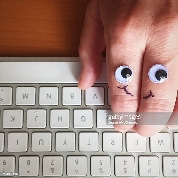 Google eyes and smiley face drawn on a hand, typing on keyboard