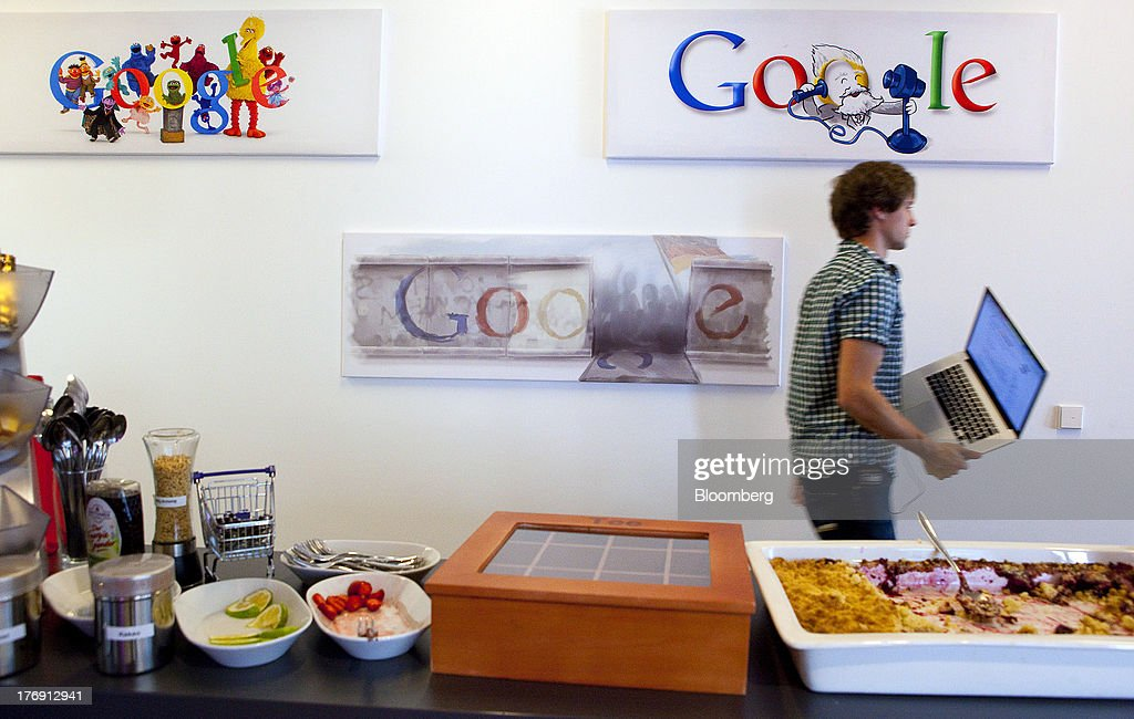 A Google Inc. employee carries an Apple Inc. laptop computer as he walks past logos inside the company's offices in Berlin, Germany, on Friday, Aug. 16, 2013. Google, based in Mountain View, California, is seeking to revive Motorola Mobility's smartphone business, recently announcing a new flagship Moto X smartphone with customizable colors that will be assembled in the U.S. Photographer: Krisztian Bocsi/Bloomberg via Getty Images