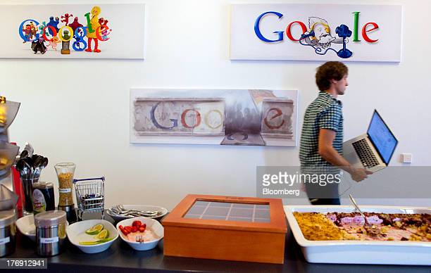 A Google Inc employee carries an Apple Inc laptop computer as he walks past logos inside the company's offices in Berlin Germany on Friday Aug 16...