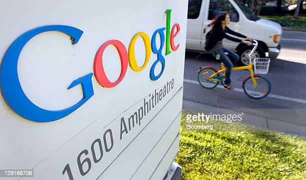 A Google Inc employee rides a 'Gbike' past signage displayed company headquarters in Mountain View California US on Thursday Oct 13 2011 Google Inc...