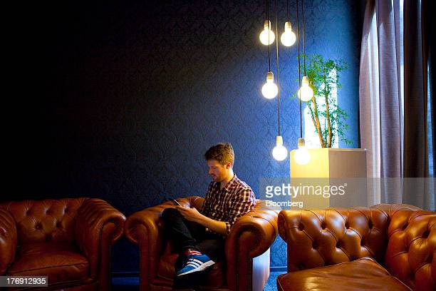 A Google Inc employee uses a personal mobile device as he sits in a leather armchair inside the company's offices in Berlin Germany on Friday Aug 16...
