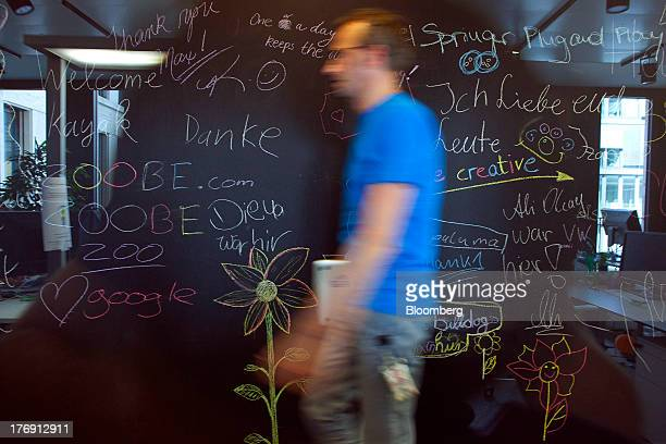 A Google Inc employee walks past a doodle covered blackboard inside the company's offices in Berlin Germany on Friday Aug 16 2013 Google based in...
