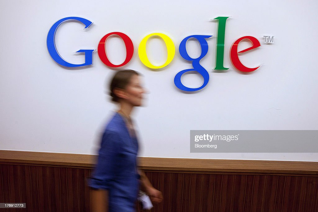 A Google Inc. employee walks past a logo outside the entrance to the company's offices in Berlin, Germany, on Friday, Aug. 16, 2013. Google, based in Mountain View, California, is seeking to revive Motorola Mobility's smartphone business, recently announcing a new flagship Moto X smartphone with customizable colors that will be assembled in the U.S. Photographer: Krisztian Bocsi/Bloomberg via Getty Images