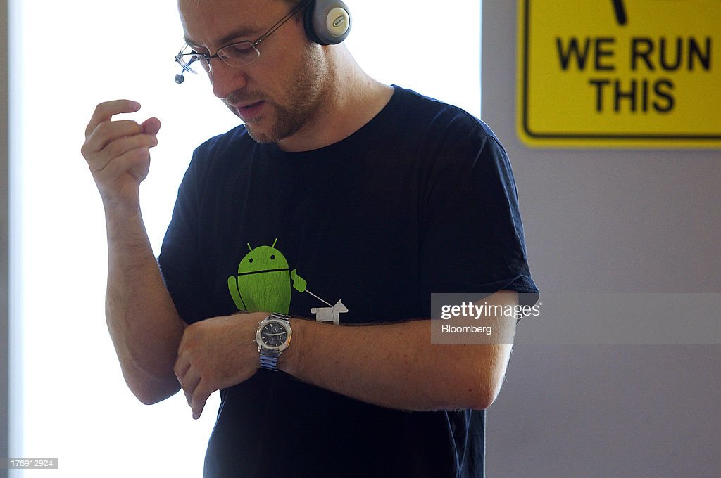 A Google Inc. employee wearing an Android operating system t-shirt gestures as he speaks on a hands-free telephone headset inside the company's offices in Berlin, Germany, on Friday, Aug. 16, 2013. Google, based in Mountain View, California, is seeking to revive Motorola Mobility's smartphone business, recently announcing a new flagship Moto X smartphone with customizable colors that will be assembled in the U.S. Photographer: Krisztian Bocsi/Bloomberg via Getty Images