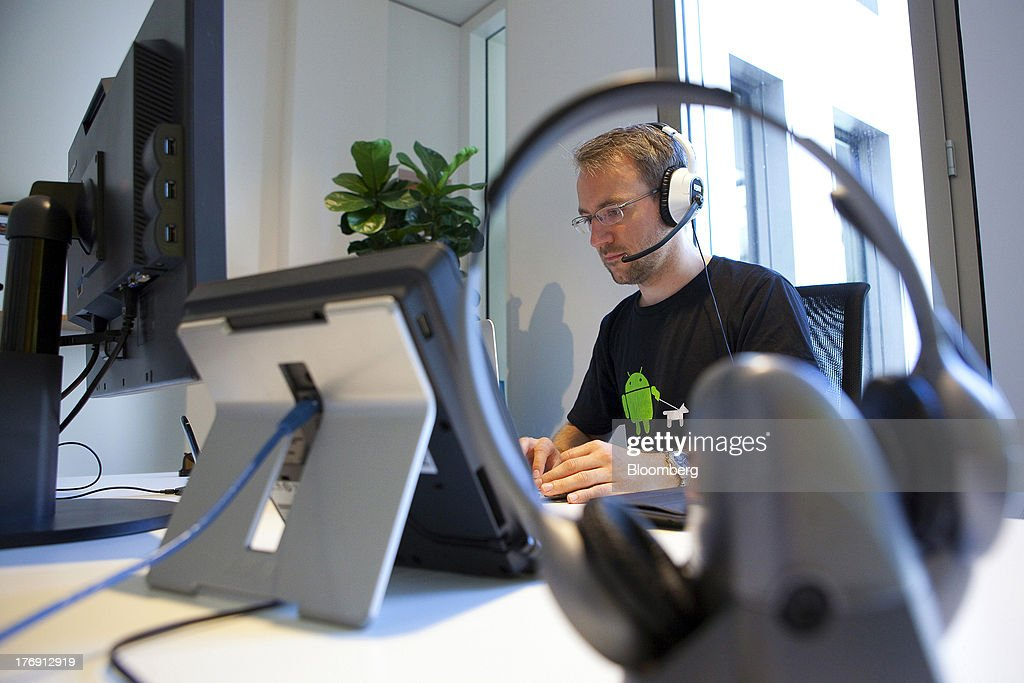 A Google Inc. employee wearing an Android operating system t-shirt works at his desk inside the company's offices in Berlin, Germany, on Friday, Aug. 16, 2013. Google, based in Mountain View, California, is seeking to revive Motorola Mobility's smartphone business, recently announcing a new flagship Moto X smartphone with customizable colors that will be assembled in the U.S. Photographer: Krisztian Bocsi/Bloomberg via Getty Images