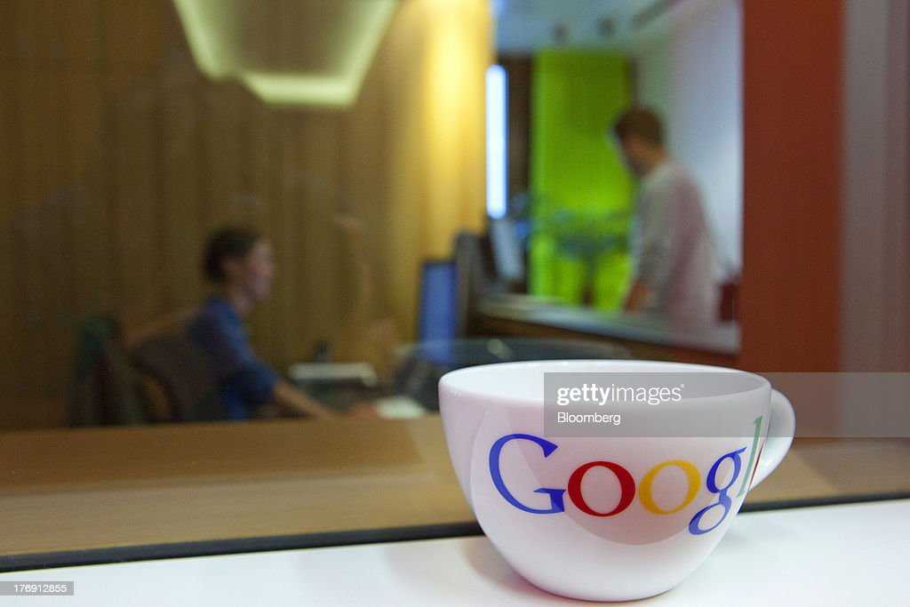 A Google Inc. logo sits on a coffee cup as employees work inside the company's offices in Berlin, Germany, on Friday, Aug. 16, 2013. Google, based in Mountain View, California, is seeking to revive Motorola Mobility's smartphone business, recently announcing a new flagship Moto X smartphone with customizable colors that will be assembled in the U.S. Photographer: Krisztian Bocsi/Bloomberg via Getty Images