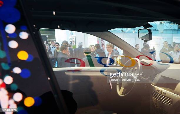 Google logo is reflected in a window of a car equiped with special cameras used to photograph whole streets can be seen on the Google streetview...