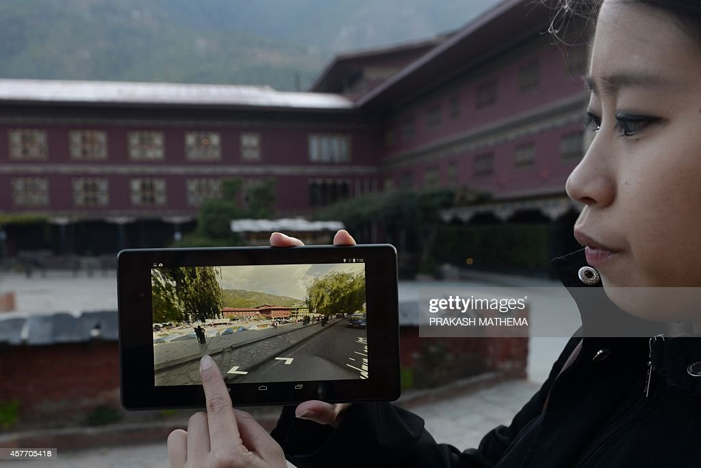 Google product communications manager Stephanie Shih demonstrates a Google Street View image on a tablet computing device in downtown Thimphu on...