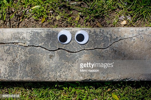 Googly Eyes on Cracked Sidewalk Making a Smiley Face : Stock Photo