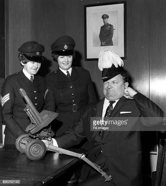 'Goon' Harry Secombe chairman of the Artistes' Branch of the Royal Artillery Association seals his ears against the blast as he 'fires' a model 105mm...