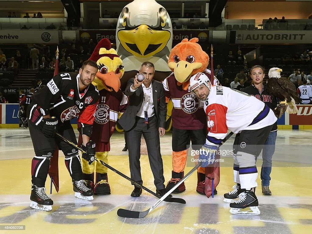 Goran Bezina of Geneve-Servette , Martin Baumann , CEO CHL with the puck in hand Gerhard Unterluggauer and of Villach SV before the Champions Hockey League group stage game between Geneve-Servette and Villach SV on August 23, 2014 in Geneva, Switzerland.