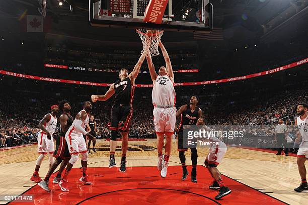 Goran Dragic of the Miami Heat and Jakob Poeltl of the Toronto Raptors go for the rebound on November 4 2016 at the Air Canada Centre in Toronto...