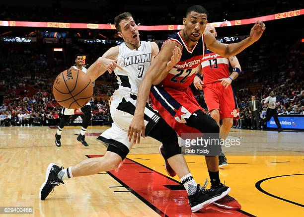Goran Dragic of the Miami Heat has the ball knocked loose by Otto Porter Jr #22 of the Washington Wizards during the first half of the game at...