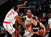Goran Dragic of the Miami Heat takes a foot to the chin as he is defended by Jeff Teague and Al Horford of the Atlanta Hawks at Philips Arena on...