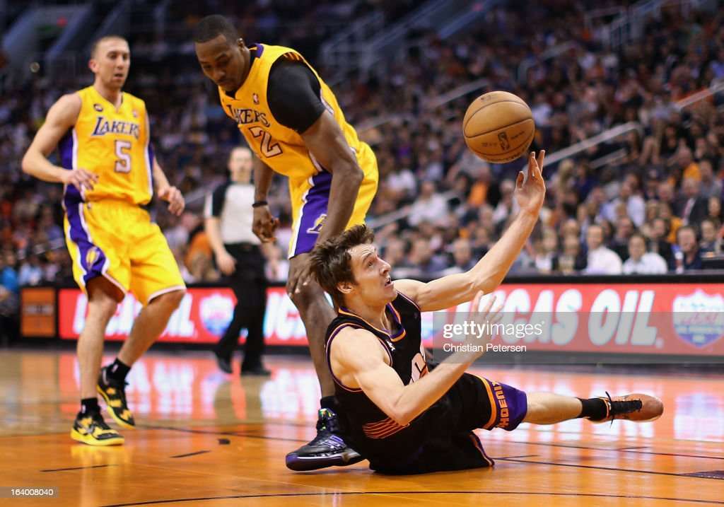 <a gi-track='captionPersonalityLinkClicked' href=/galleries/search?phrase=Goran+Dragic&family=editorial&specificpeople=4452965 ng-click='$event.stopPropagation()'>Goran Dragic</a> #1 of the Phoenix Suns attempts a shot as he falls to the court past <a gi-track='captionPersonalityLinkClicked' href=/galleries/search?phrase=Dwight+Howard&family=editorial&specificpeople=201570 ng-click='$event.stopPropagation()'>Dwight Howard</a> #12 of the Los Angeles Lakers during the second half of the NBA game at US Airways Center on March 18, 2013 in Phoenix, Arizona. The Suns defeated the Lakers 99-76.