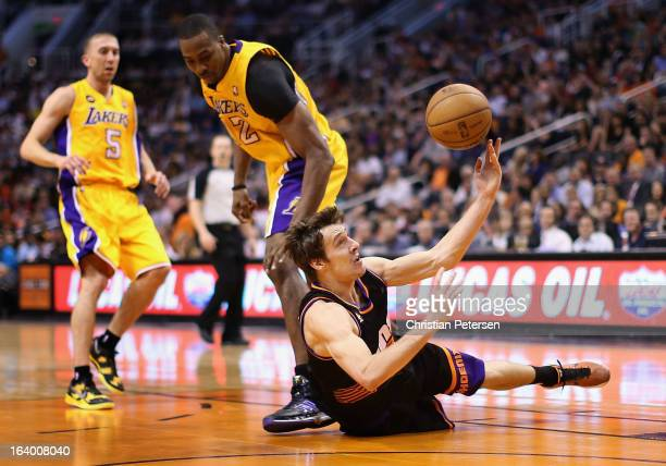 Goran Dragic of the Phoenix Suns attempts a shot as he falls to the court past Dwight Howard of the Los Angeles Lakers during the second half of the...