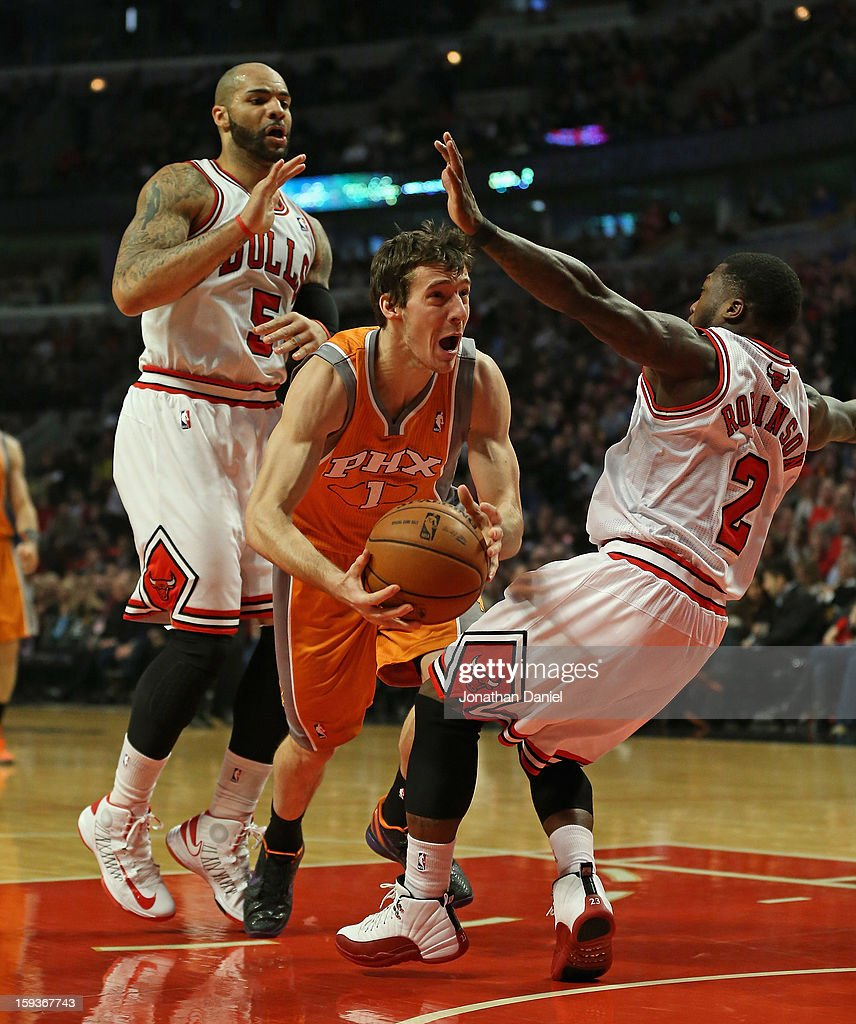 Goran Dragic #1 of the Phoenix Suns falls as he tries to move between Carlos Boozer #5 and Nate Robinson #2 of the Chicago Bulls at the United Center on January 12, 2013 in Chicago, Illinois.