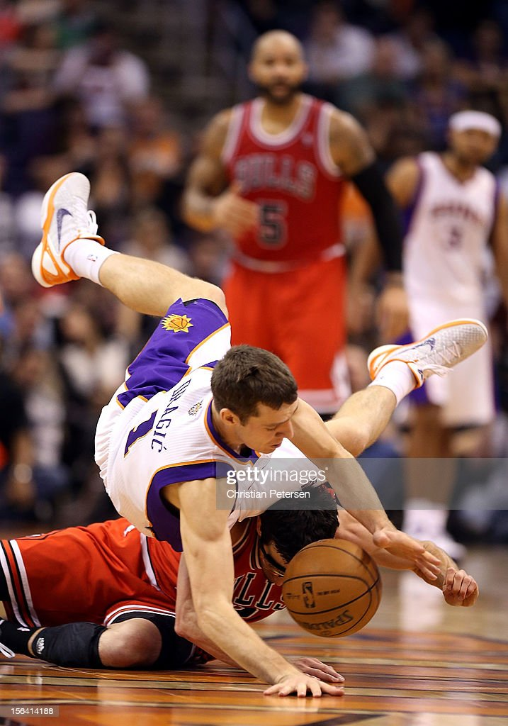 <a gi-track='captionPersonalityLinkClicked' href=/galleries/search?phrase=Goran+Dragic&family=editorial&specificpeople=4452965 ng-click='$event.stopPropagation()'>Goran Dragic</a> #1 of the Phoenix Suns falls over <a gi-track='captionPersonalityLinkClicked' href=/galleries/search?phrase=Kirk+Hinrich&family=editorial&specificpeople=201629 ng-click='$event.stopPropagation()'>Kirk Hinrich</a> #12 of the Chicago Bulls as the battle for a loose ball during the NBA game at US Airways Center on November 14, 2012 in Phoenix, Arizona. The Bulls defeated the Suns 112-106 in overtime.